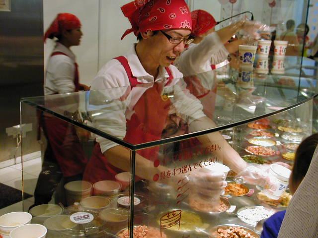 インスタントラーメン発明記念館(大阪池田市)オリジナルカップラーメンの具材を入れてくれるスタッフさん
