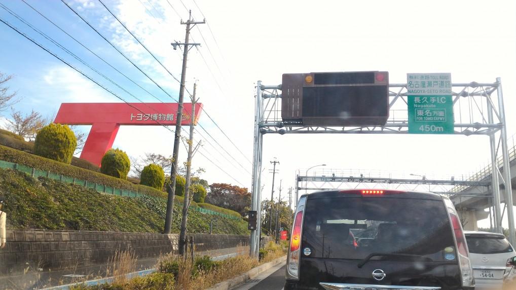 「トヨタ博物館」の赤いTの看板が車道から