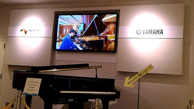 新東名浜松SA内のヤマハのコーナーグランドピアノ工場のバーチャルツアー案内の柳家花緑さんが演奏しているところ