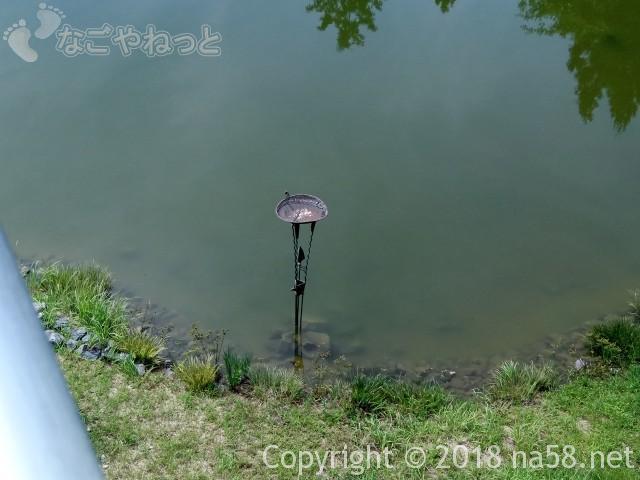三重県菰野町「希望荘」山頂館のデッキで、こころ池コインを投げ入れる