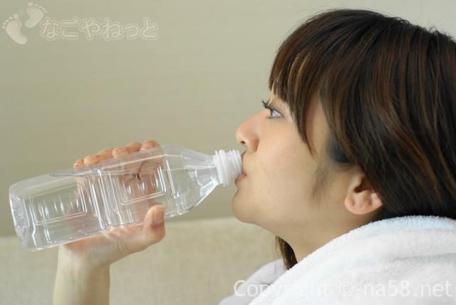 入浴前後の水分補給でベストなタイミング、ペットボトルの水分を飲む女性画像