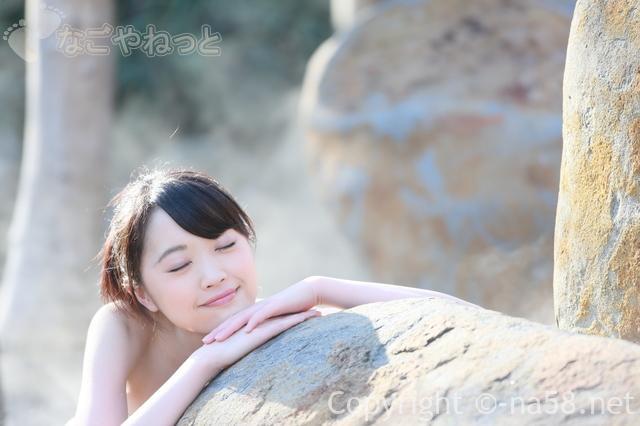 露天風呂で目を閉じてくつろぐ若い女性