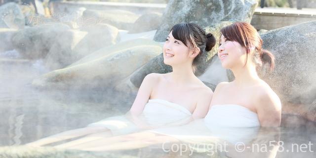 若い女性二人が露天岩風呂に入ってくつろいでいる画像