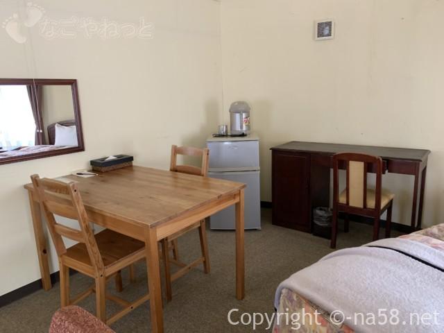 伊豆市時之栖のコテージホテル「オリーブの木」のコテージ内テーブル椅子、冷蔵庫