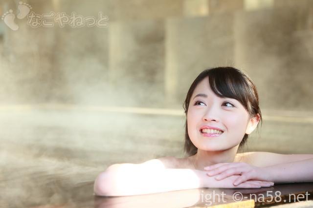 温泉につかって笑顔の女性