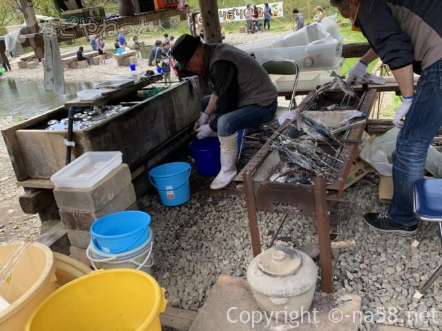 國田家の芝桜(岐阜県郡上市)、釣り堀のそばアユ塩焼きする男性