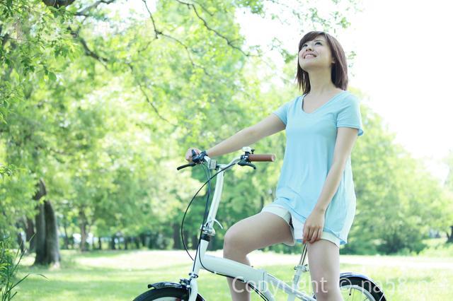 木漏れ日をあび自転車にのる女性