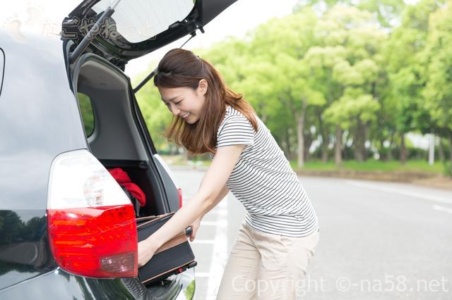 車でドライブ旅行、レジャーに、荷物を載せる女性