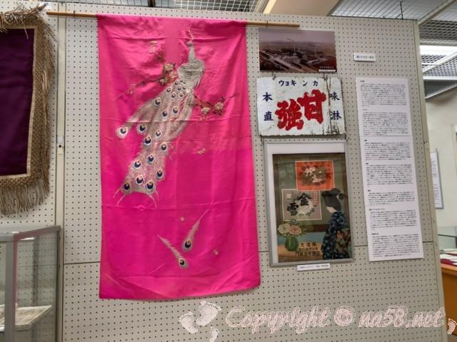 蟹江町歴史民俗資料館(愛知県蟹江町)特別展示会場内、甘強酒造の古い看板やポスター、孔雀の刺繍