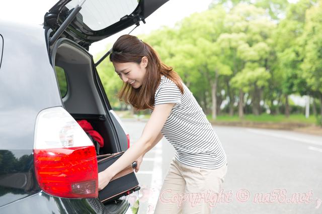 車の後ろから荷物を下ろす若い女性