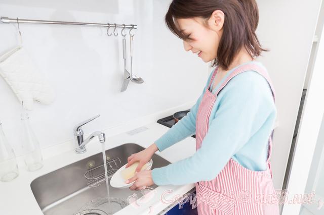 台所キッチンで食器を洗う女性