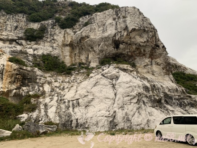 道の駅白崎海洋公園(和歌山県由良町)の駐車場の車と白い石灰岩の巨岩